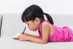 Niña china asiática que pone en el libro de la escritura del sofá Fotografía de archivo