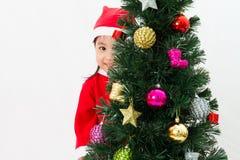 Niña china asiática que presenta con el árbol de navidad Fotos de archivo