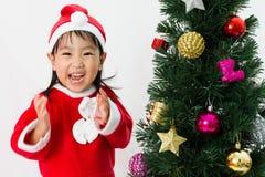 Niña china asiática que presenta con el árbol de navidad Imagenes de archivo