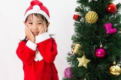 Niña china asiática que presenta con el árbol de navidad Imágenes de archivo libres de regalías