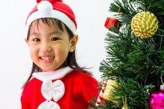 Niña china asiática que presenta con el árbol de navidad Fotografía de archivo libre de regalías