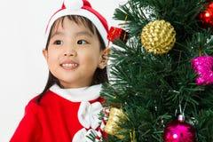 Niña china asiática que presenta con el árbol de navidad Foto de archivo