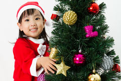 Niña china asiática que presenta con el árbol de navidad Imagen de archivo libre de regalías