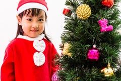 Niña china asiática que presenta con el árbol de navidad Foto de archivo libre de regalías