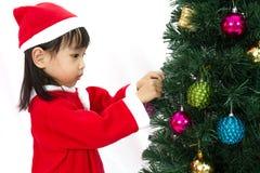 Niña china asiática que presenta con el árbol de navidad Fotografía de archivo