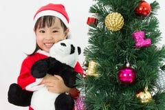 Niña china asiática que sostiene la muñeca de la panda que presenta con Christm Imágenes de archivo libres de regalías