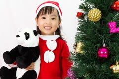 Niña china asiática que sostiene la muñeca de la panda que presenta con Christm Imagen de archivo libre de regalías