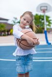 Niña con baloncesto en corte en tropical Imagen de archivo