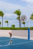 Niña con baloncesto en corte en tropical Foto de archivo libre de regalías