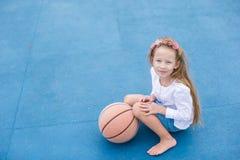 Niña con baloncesto en la corte al aire libre Imagenes de archivo