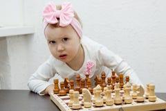 Niña con el arco rosado que juega a ajedrez Fotografía de archivo