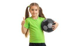 Niña con el balón de fútbol en las manos que miran la cámara que muestra los pulgares para arriba Foto de archivo