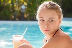 Niña con el cóctel en piscina Imagenes de archivo