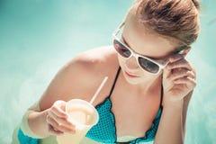 Niña con el cóctel y las gafas de sol en piscina Imágenes de archivo libres de regalías