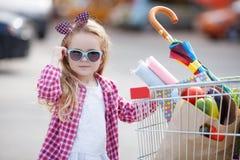 Niña con el carro de la compra con los productos Foto de archivo