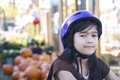 Niña con el casco de la bici en la bicicleta Imagen de archivo