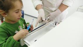 Niña con el dentista tomado de la caja sistemas para la anestesia dental almacen de metraje de vídeo