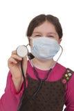 Niña con el estetoscopio y la máscara quirúrgica Imágenes de archivo libres de regalías