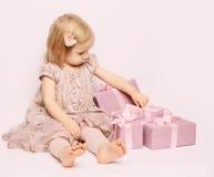 Niña con el fondo rosado del cumpleaños de la caja de regalo Foto de archivo