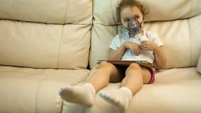 Niña con el inhalador en el sofá metrajes