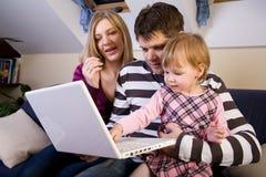 Niña con el juego de los padres con un ordenador portátil fotografía de archivo