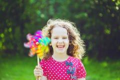 Niña con el juguete del molinillo de viento del arco iris en parque del verano Eco, trave fotos de archivo