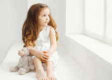 Niña con el juguete del oso de peluche en casa en el sitio blanco Foto de archivo libre de regalías