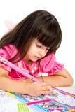 Niña con el lápiz que miente en suelo. aislado Imagen de archivo