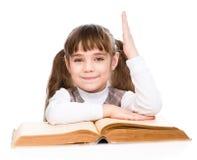 Niña con el libro que aumenta la mano que conoce la respuesta a la pregunta En el fondo blanco Fotografía de archivo