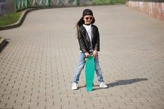 Niña con el monopatín en la calle Foto de archivo libre de regalías