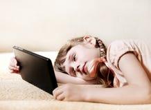 Niña con el ordenador de la tablilla Foto de archivo