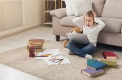 Niña con el ordenador portátil que se sienta en el piso en casa Fotos de archivo libres de regalías