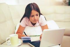 Niña con el ordenador portátil y los auriculares en casa Fotografía de archivo libre de regalías