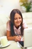 Niña con el ordenador portátil y los auriculares en casa Foto de archivo libre de regalías