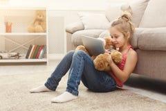 Niña con el oso de la tableta y de peluche en casa Imagenes de archivo