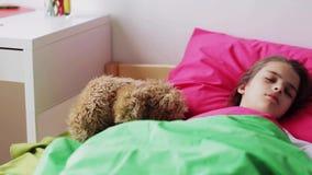 Niña con el oso de peluche que duerme en casa almacen de video