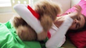 Niña con el oso de peluche que duerme en casa metrajes