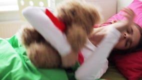 Niña con el oso de peluche que duerme en casa almacen de metraje de vídeo