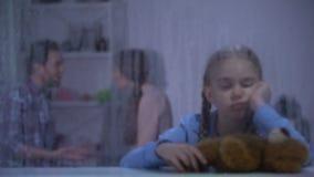 Niña con el oso de peluche que no muestra ningún gesto en el día lluvioso, padres que pelean almacen de metraje de vídeo