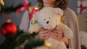 Niña con el oso de peluche que se coloca cerca de árbol de abeto adornado en el colegio de internos metrajes