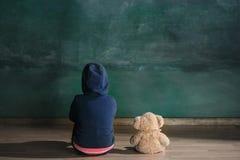 Niña con el oso de peluche que se sienta en piso en sitio vacío Concepto del autismo imagen de archivo
