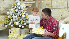 Ni?a con el padre que desempaqueta las cajas de regalo cerca del ?rbol de navidad en casa almacen de video