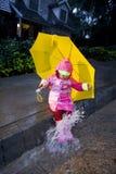 Niña con el paraguas amarillo que juega en la lluvia 4 Imágenes de archivo libres de regalías