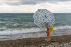 Niña con el paraguas en la playa en mún tiempo imagenes de archivo