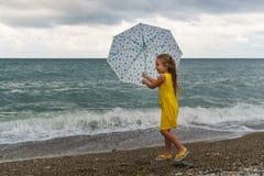 Niña con el paraguas en la playa en mún tiempo foto de archivo