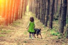 Niña con el paseo del perro en el bosque Fotografía de archivo