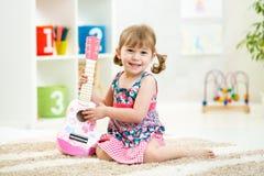 Niña con el regalo del juguete de la guitarra Foto de archivo