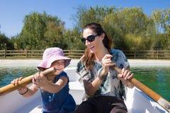 Niña con el rowing del sombrero y de la madre en un barco Foto de archivo libre de regalías