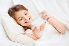 Niña con el smartphone que juega en cama Fotografía de archivo