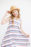 niña con el sombrero de paja y el vestido rayado contra un fondo blanco Cabritos felices Imagen de archivo